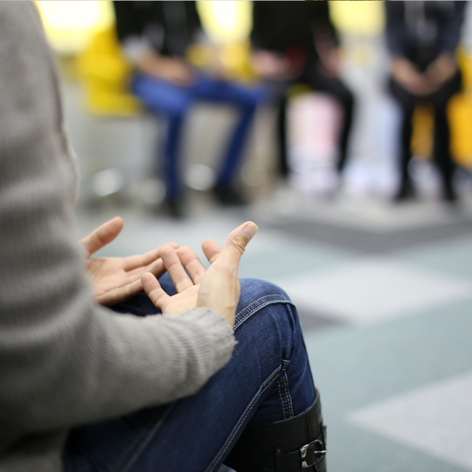 Close up of hands on lap of client in circle depicting Group Services